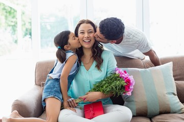 Woman receiving kiss from her family