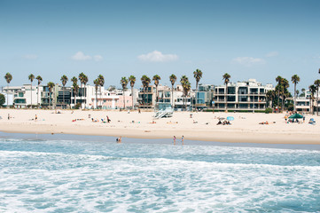 Pacific ocean coastline in Los Angeles USA. People walking at the beach. Rental buildings on Venice beach.