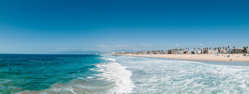 Pacific ocean coastline in Los Angeles USA. People walking at the beach. Ocean waves and foam.