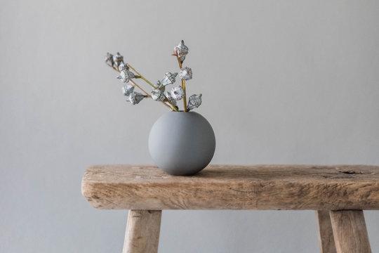 eukalyptus zweig in runder vase auf altem  holzschemel vor grauer wand
