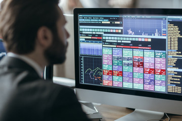 Man broker analyizing chart and stock market performance forecas