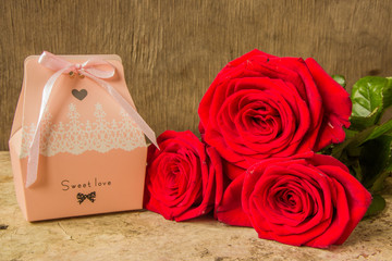 Red roses and gift covered craft paper