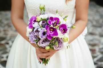 the bride holding a purple bouquet. wedding flowers. soft focus.