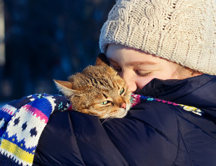 Smiling young girl holding her cat outdoors.