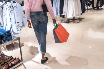 black woman shopping in a shopping center with bags