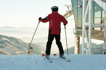 Skier preparing for a downhill ride from the top of a mountain