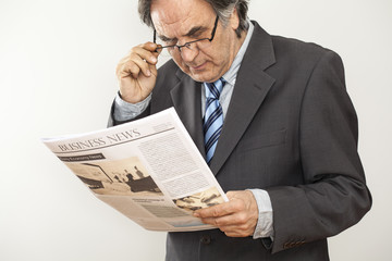 Businessman reading newspaper on gray background