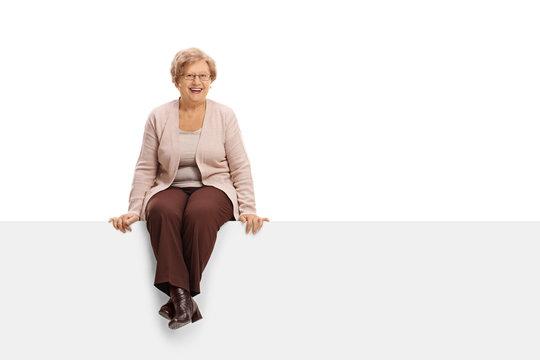 Joyful mature woman sitting on a panel