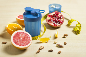 Fitness and healthy life concept. Fruits and nuts on a wooden table. Fitness equipment. Shaker and supplement measuring tape on a table.