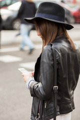 Young stylish woman using a mobile phone in the street