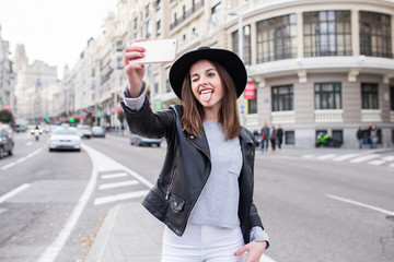 Young stylish woman taking photos with a phone in the street