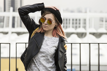 Portrait of young woman in hipster glasses,pot hat and black leather jacket standing and looking forward in city