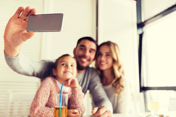 close up of family taking selfie at restaurant
