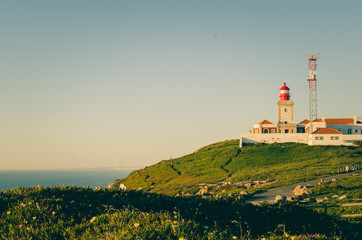 Nice view of a lighthouse with the ocean and green field in Cabo da Roca, Portugal