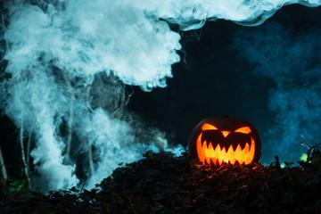 Scary Illuminated Halloween Pumpkin in Dark Smoky Background