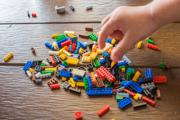 coloured plastic construction blocks or brick toy with Child hands.(Selective focus)