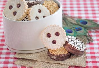 Kekse in weißer Keramikdose auf karierter Tischdecke