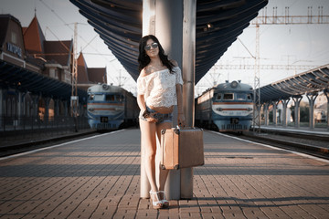 a lonely young brunette woman with an old suitcase is standing on the station platform