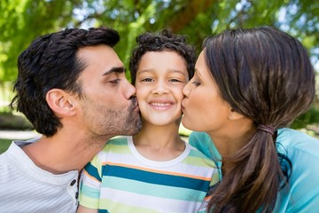 Boy being kissed by his parents in park