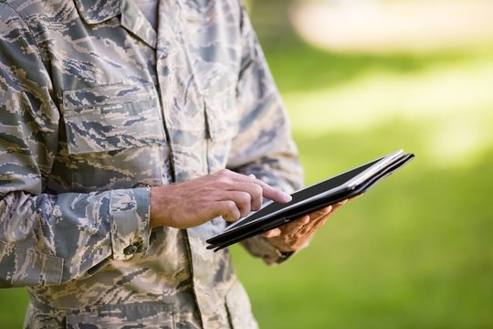 Mid-section of soldier using digital tablet in park