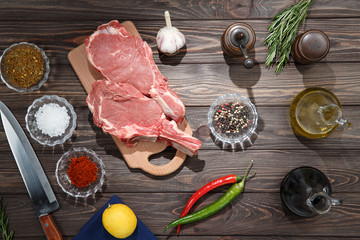 Raw beef steaks with spices on wooden background