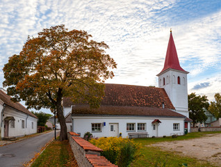 Old white stoned Lutheran church and tree in Haapsalu, Estonia