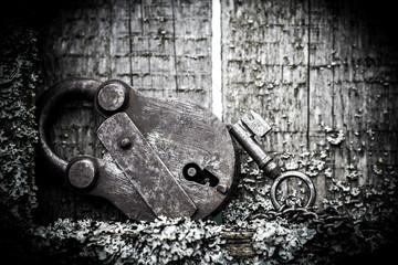Metal padlock lying on a wooden Board.