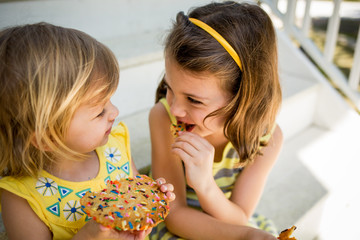 Two young girls sharing a cookie, close up