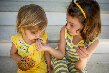 Sisters eating cookies while sitting together on stairs