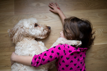 Girl and dog lying on wood floor, face to face