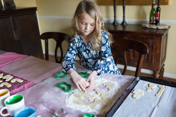 Young girl making cookies with festive cutters