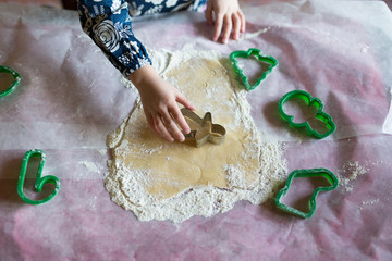 Childs hands making cookies with festive cutters