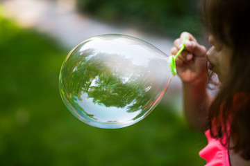 Young girl blowing soap bubble
