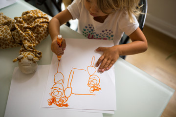 Child drawing orange colour figures on paper
