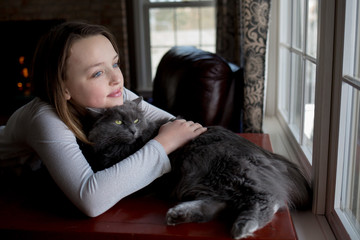Girl and cat cuddling, looking through window