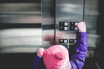 Young girl pressing elevator button