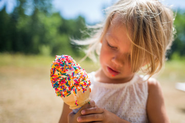 Child holding and looking at ice cream with sprinkles