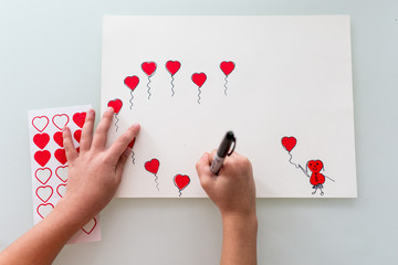Overhead view of child drawing heart balloons on paper