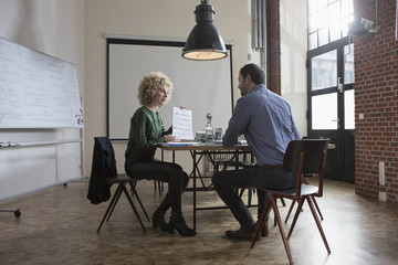 Man and woman discussing paper in boardroom