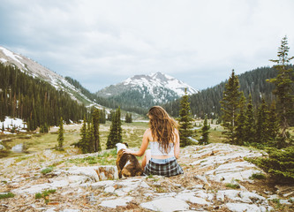 Woman sitting on rocks with dog with mountains