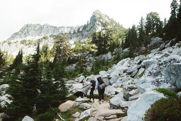 Two people and dog walking in mountain terrain