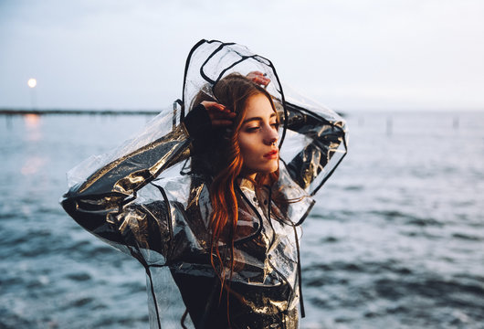 Young woman in a  clear plastic mac standing by the sea