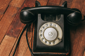 old telephone with wire on a wooden background, retro