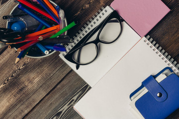 glasses lie on a notepad, blue card, pens and pencils