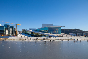 Oslo Opera house with walking and relaxing people at sunny winter day