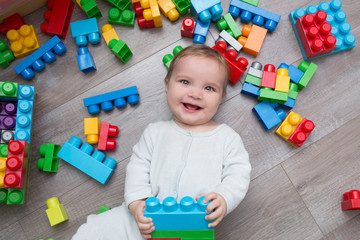 Little baby playing with lots of colorful plastic blocks constructor on floor in the room.