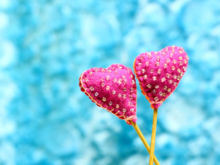 Decorative hand made two hearts on blue sky background. Sewed from a felt and decorated with beads. Beautiful congratulation card background for St. Valentine`s day.