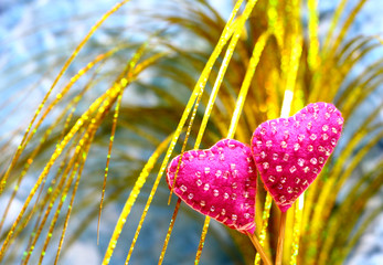 Decorative hand made two hearts on colorful background. Sewed from a felt and decorated with beads. Beautiful congratulation card background for St. Valentine`s day. Copyspace.