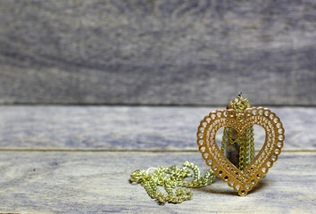Golden heart on a chain and colored stones, minerals in the bottle on wooden background. Beautiful congratulation card background for St. Valentine`s day. Copyspace.