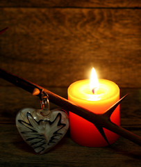 Prickly branch, glass heart and burning candle on wooden background. Beautiful congratulation card background for St. Valentine`s day. Copyspace.